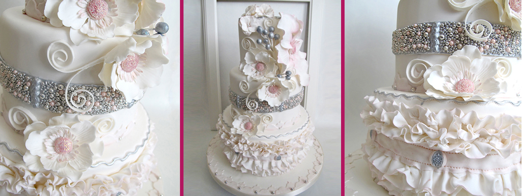 White wedding cake with blush pink and white flowers and silver accents