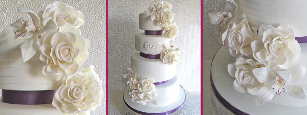 White cake with a layered pattern and White roses and Orchids with purple ribbon
