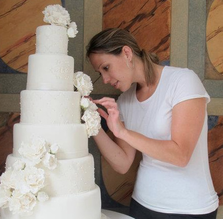 Wendy working on a six tier white wedding cake with peonies.